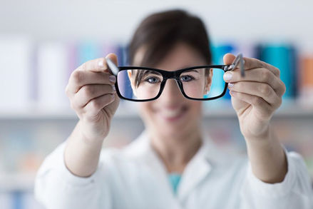 Optician holding a pair of eyeglasses